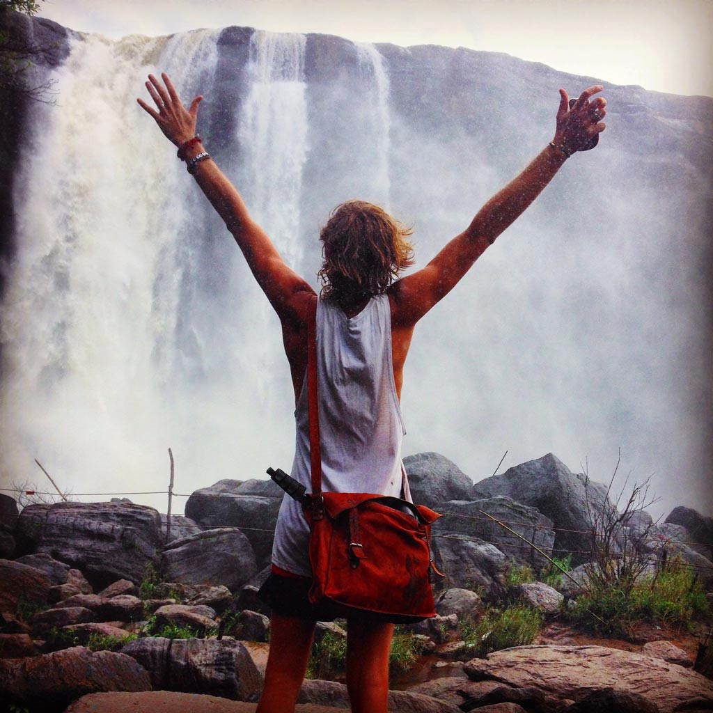 Phil Haley with arms up looking at a waterfall